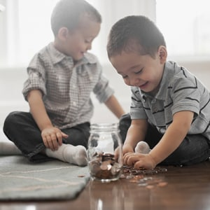 Stock photo two children playing with coins dropping them into glass jars