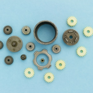 Metal and palstic gears of dismantled mechanism laying on blue background