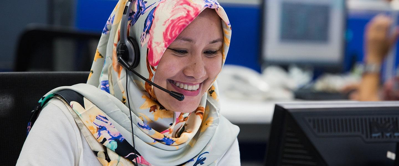 woman set at computer using headset