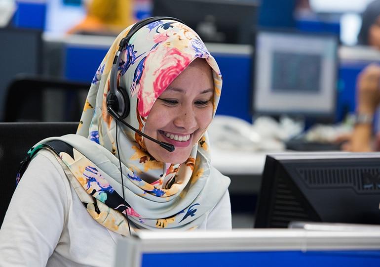 Woman sat at computer using headset