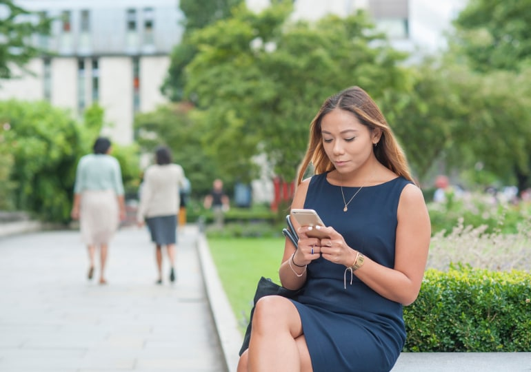 Woman sitting on bench using phone