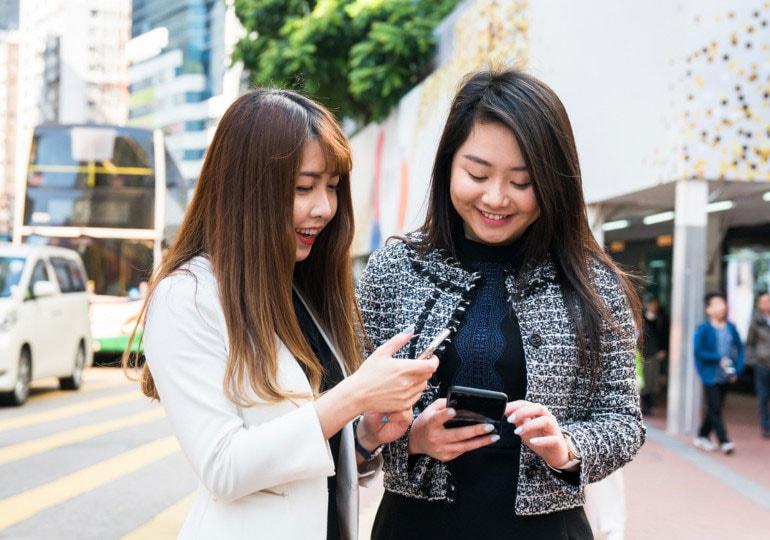 2 people using phones outside