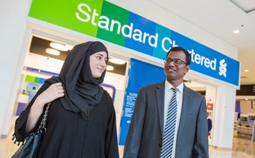 Two people walking outside a Standard Chartered branch