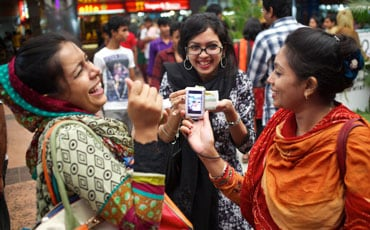 Three females chatting and viewing something on mobile