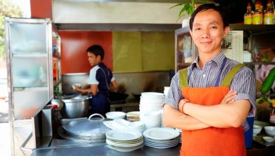 Man working as cook in Asian restaurant kitchen