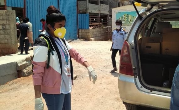 woman loading car while wearing face mask