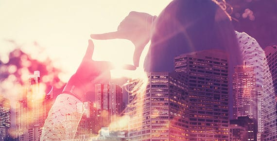 Double exposure of a skyline and a woman creating a frame with her fingers
