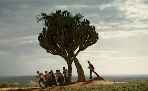 Children running past a tree