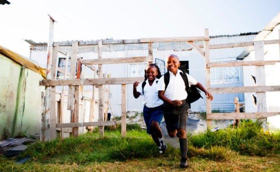 Excited young brother and sister running from their township