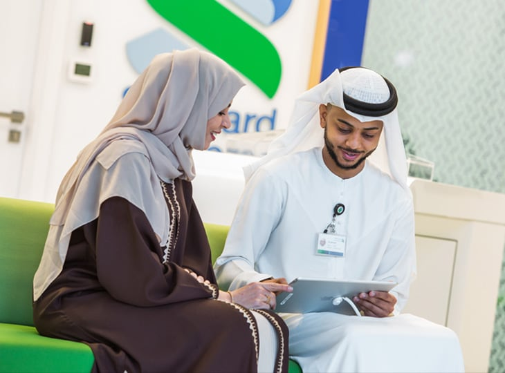 Staff member helping an Islamic Banking client using an iPad
