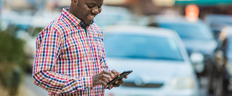 man using phone while crossing traffic