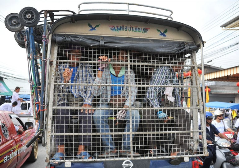 people behind cage on back of bus