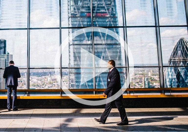 man walking past large window