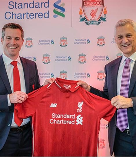 2 men holding LFC shirt