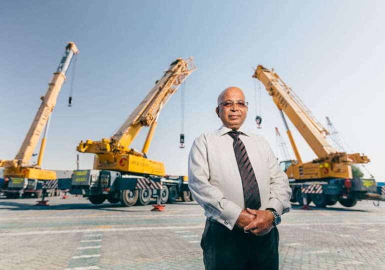 man standing in front of cranes