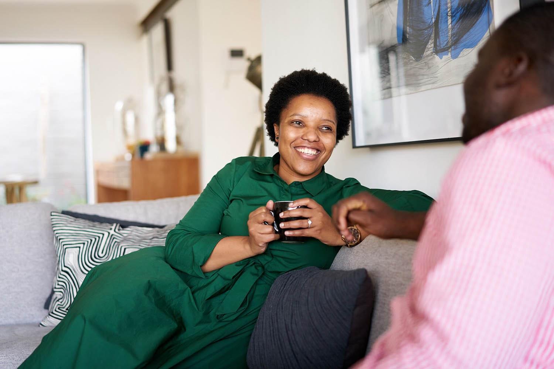 Lady smiling sat on sofa holding a mug