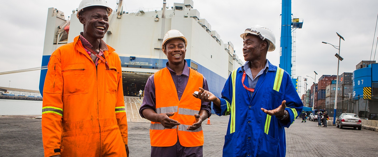 3 workers standing in front of ship