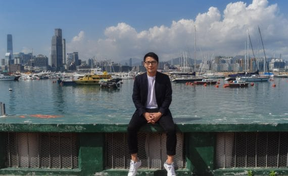 William Luk sitting in front of harbor