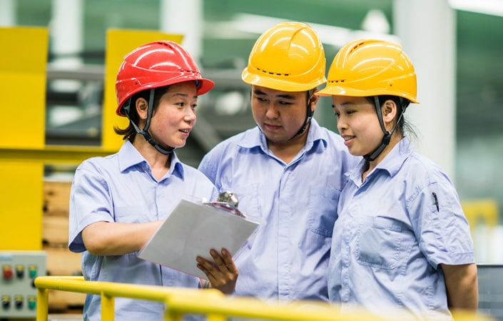 Three people in factory wearing hard hats