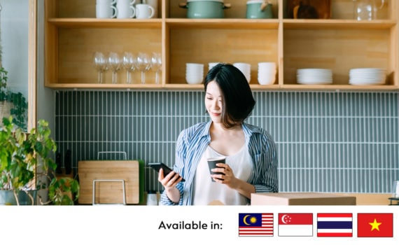 woman using phone and holding cup
