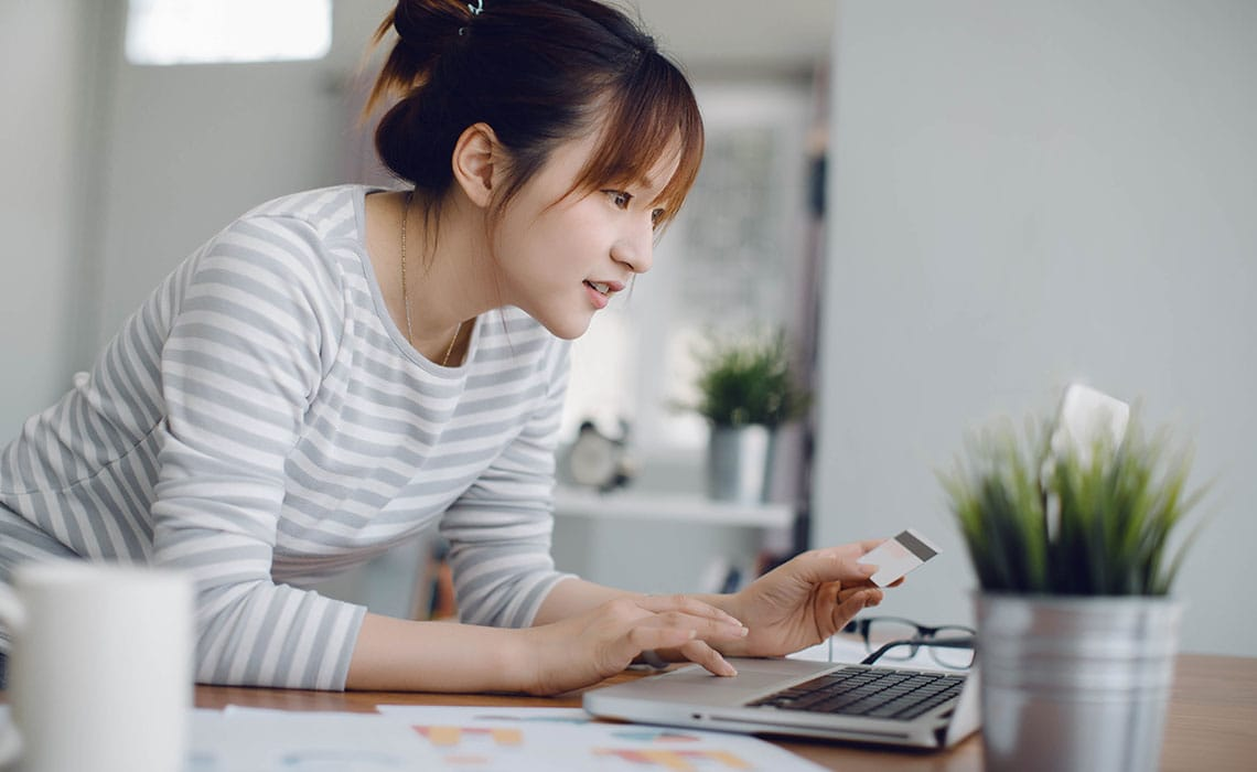 woman looking at laptop holding credit card