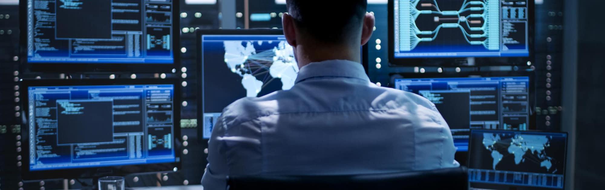 Man looking at bank of computer screens