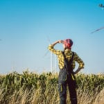 Flannel shirted farmer stands on the edge of cornfield watching turbines