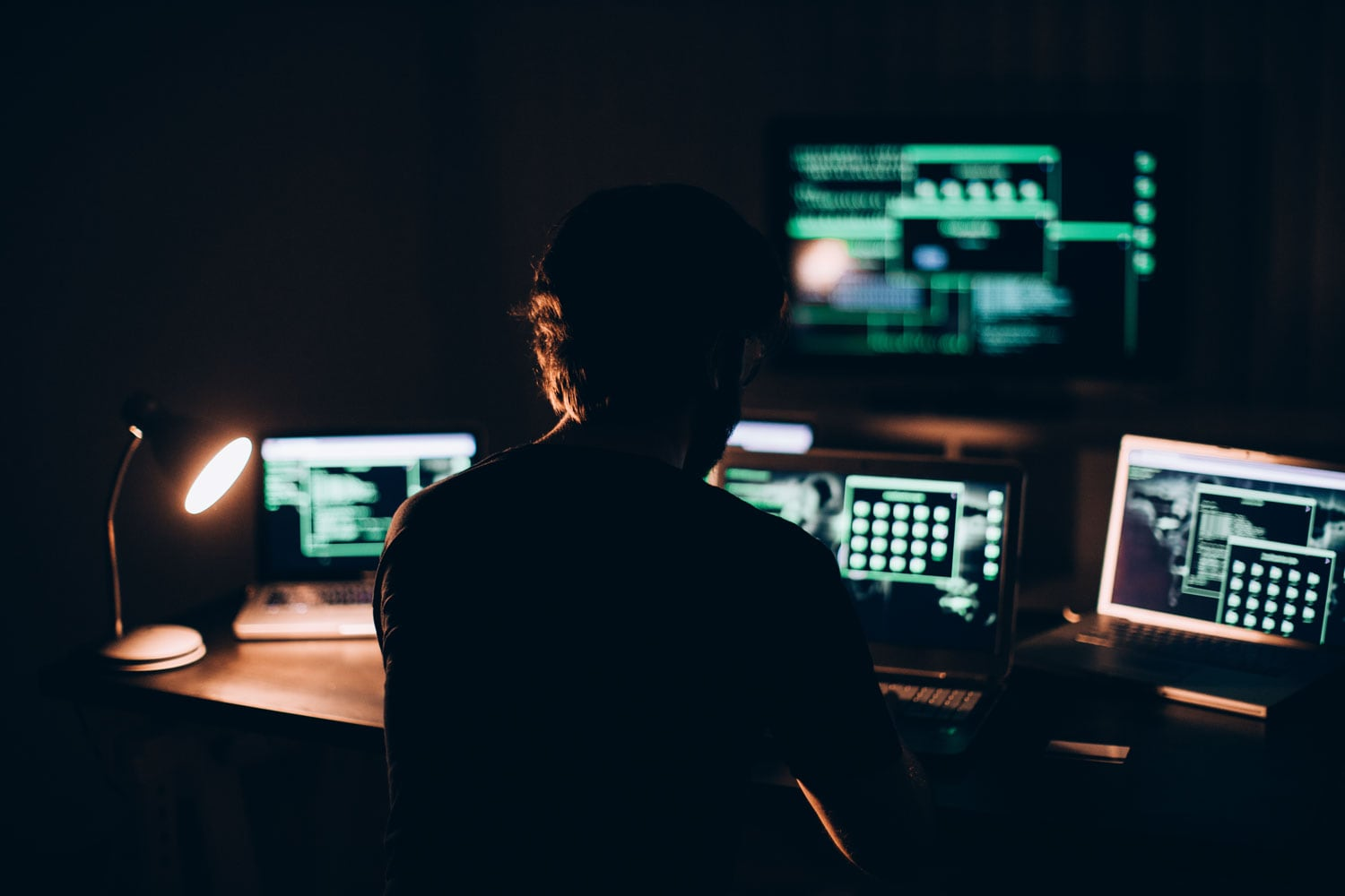 man sitting in front of computers in dark room