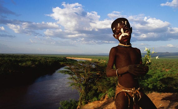 Child with flowers overlooking the Omo River, Omo Valley, Ethiopia