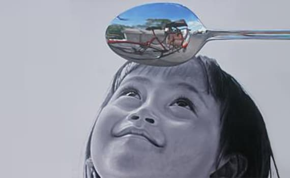 Girl looking at a reflection in a spoon