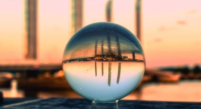 a crystal ball showing the reflection of the city view by the sea