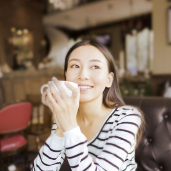 a lady holding a coffee cup in a cafeteria