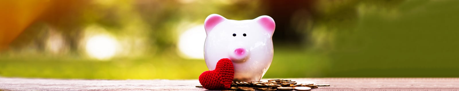 a pink piggy bank with a wool-made heart decorations and coins spread on the gorund