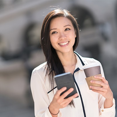 a lady holding a mobile phone and a cup of coffee she just redeemed with points