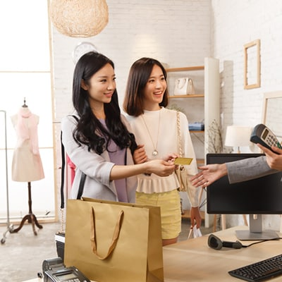 2 ladies shopping with a golden credit card, to earn 360 rewards while spending