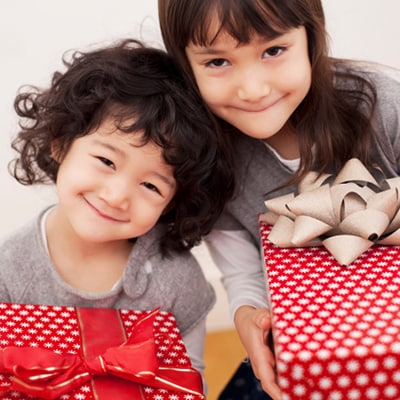 brother and sister holding a gift box and smiling