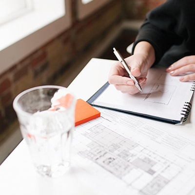 a person writing on notebook with pagers, memo pad and a glass on the desk