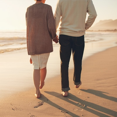 a gentleman and a lady holding hands walking on the beach