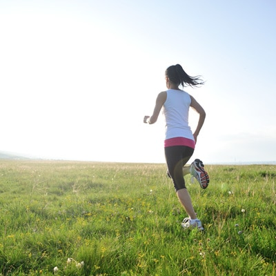 a lady running in a grass field