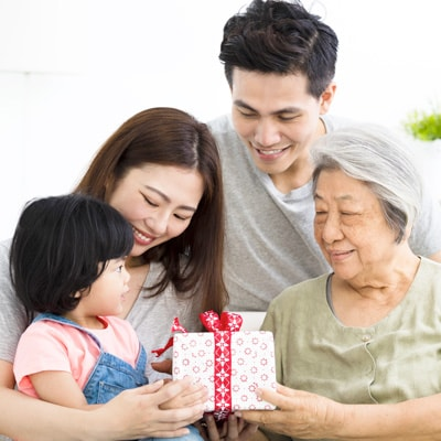 a family with a old lady, parents, and a kid holding a gift with red ribbon