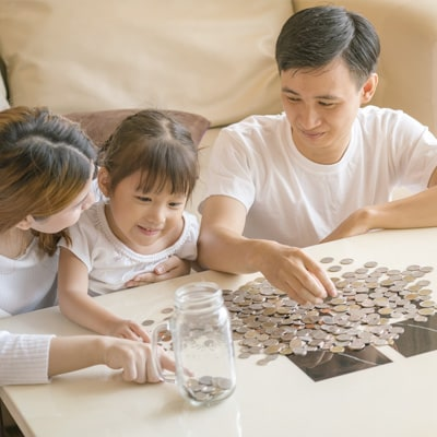 family counting coins and putting it into a glass jar.