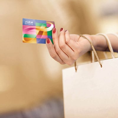 a lady's hand holding an octopus card and paper shopping bag