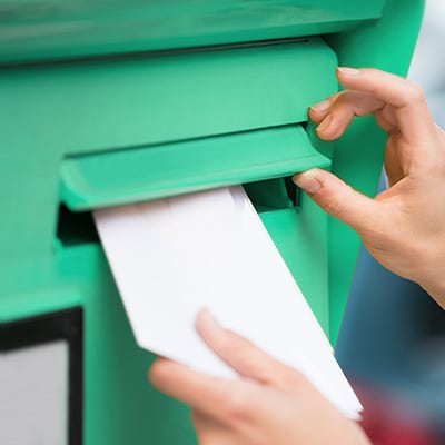 a person putting letters into a green postbox
