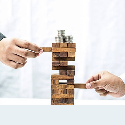 2 people playing jenga, with 3 stacks of coins on the top