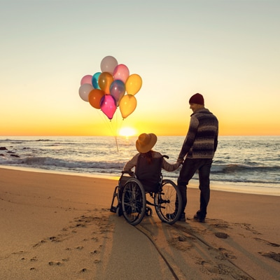 a disabled on a wheelchair and holding balloons with a man on the beach when sunset