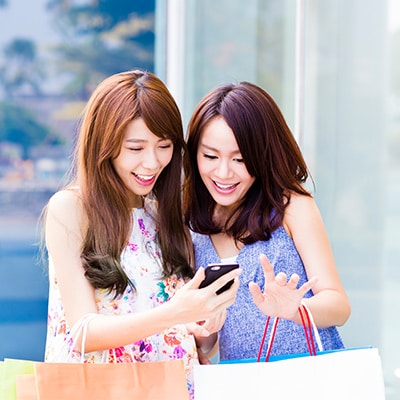 2 ladies using mobile phone while shopping