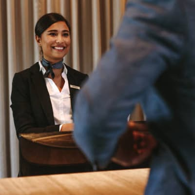 a lady in suit standing at the concierge