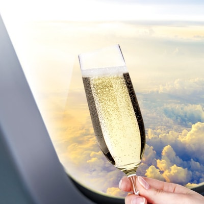 holding a champagne in the flight cabin