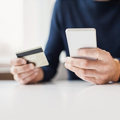 man holding mobile and a credit card