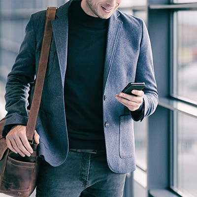 a gentleman in suit using mobile phone while walking
